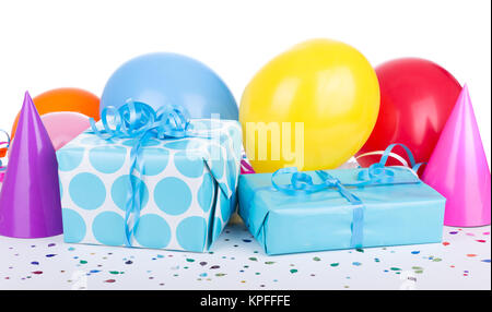 Blue birthday presents with balloons and party hats on white background - Stock Photo