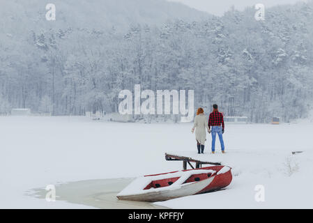 The back view of the loving couple holding hands in the front of the boat covered with snow. Village location. - Stock Photo