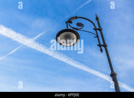 Street lamp and contrails - Stock Photo