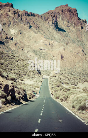 lava rocks and road in national park el teide on canary island of tenerife - Stock Photo