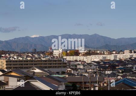 Mount Fuji seen over suburban houses and apartments buildings in Tsukushino, Machida, Tokyo, Japan. Friday November - Stock Photo