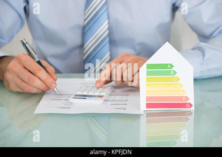 Businessman Calculating Energy Efficiency Rate - Stock Photo
