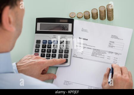 Businessperson Calculating Invoice With Coins At Desk - Stock Photo