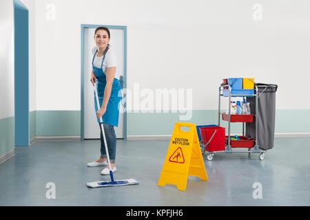 Female Janitor Mopping Corridor - Stock Photo