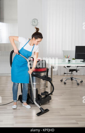 Female Janitor Cleaning Floor With Vacuum Cleaner - Stock Photo