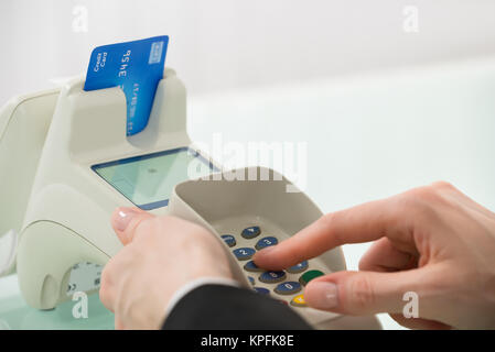 Woman Pressing Button On Credit Card Machine - Stock Photo
