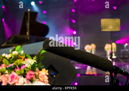 close up on a microphone during recording session with a singer piano in the background music studio - Stock Photo