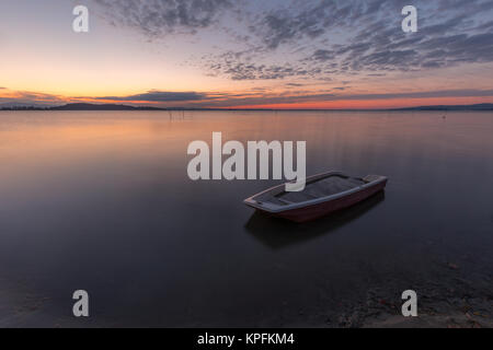 A little fishing boat in the middle of perfectly still water at sunset, with mackerel clouds sky (Trasimeno lake, - Stock Photo