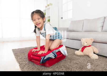 happy beautiful little kid girl kneeling on suitcase face to camera and pressing trying to closing overfilled travel - Stock Photo