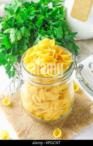Culinary background with conchiglie pasta on wooden table. Pasta in the form of cockleshells in a glass jar with - Stock Photo