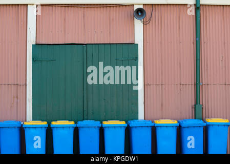 A number of wheely bins lined up outside a colourful tin shed in regional Australia - Stock Photo