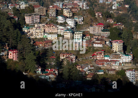 Apartment buildings and houses on side of mountain in Shimla, India - Stock Photo
