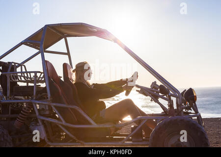 Woman driving quadbike in sunset. - Stock Photo