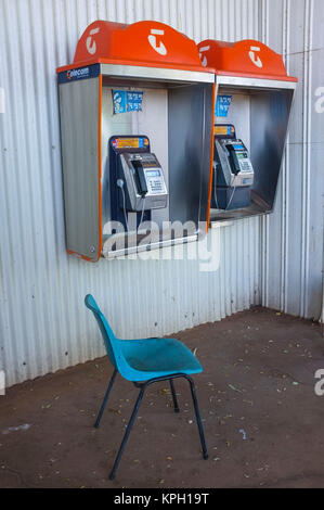 A blue chair in front of two public phone from the Telstra company in the Australian Outback. Telstra is the Australian - Stock Photo