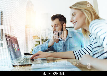 Couple of young perspective workers using laptop and looking like thoughtfully. - Stock Photo