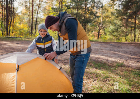father and son putting up tent - Stock Photo