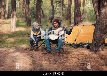 father and son with guitar in forest - Stock Photo