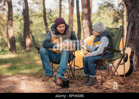 father and son eating in forest - Stock Photo