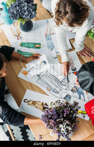 fashion designers working with sketches - Stock Photo