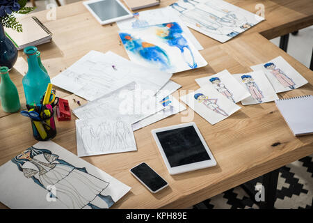digital devices and sketches on table - Stock Photo