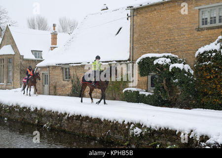 Young women riding horses through Lower Slaughter village in the snow in December. Lower Slaughter, Cotswolds, Gloucestershire, - Stock Photo
