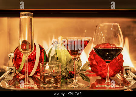 Multiple types of alcoholic drinks with Christmas holiday decorations by a fireplace - Stock Photo