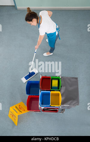Female Janitor Mopping Floor - Stock Photo