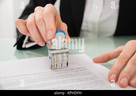 Businesswoman Hand Stamping Paper With Date Stamper - Stock Photo