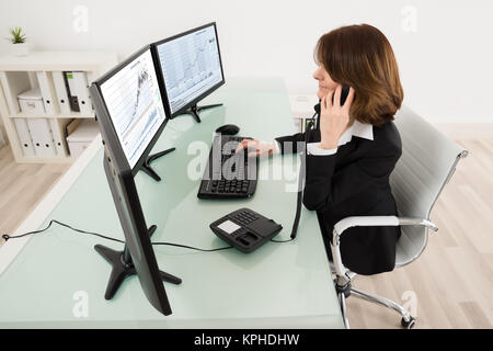 Young Female Stock Market Broker Working On Multiple Computers - Stock Photo
