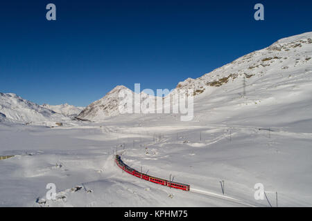 Red train of Bernina. Unesco heritage, Bernina express, winter landscape - Stock Photo