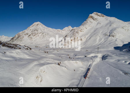 Red train of Bernina, aerial photo. Engadine Valley covered with snow - Stock Photo