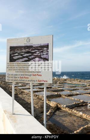 An information  sign at Salt Pans on the coast at Qbajjar  near Marsalforn Bay Bay Gozo Malta - Stock Photo