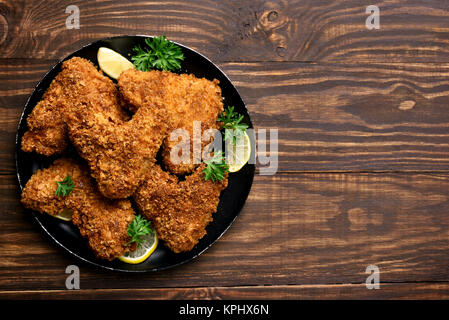 Fried breaded chicken wings on plate over wooden background with copy space. Top view, flat lay food - Stock Photo