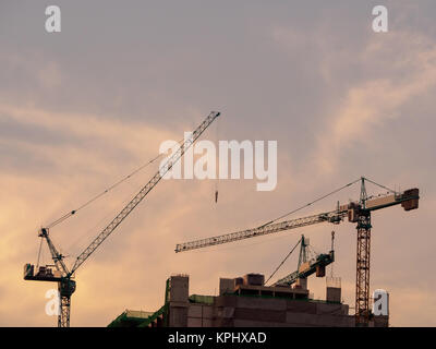 Construction site.Three Construction cranes and high-rise building under construction at sunset. - Stock Photo