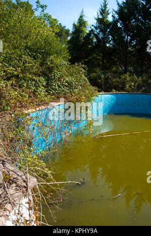 detail of abandoned and overgrown swimming pool - Stock Photo