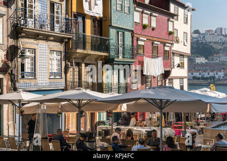 Cafe bars and traditional old, tiled houses on the waterfront in the Ribeira district of Porto, Portugal - Stock Photo