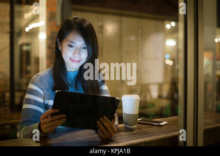 Asian woman look at tablet pc in cafe - Stock Photo