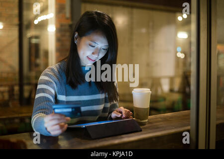 Asian young woman using tablet for online shopping in cafe - Stock Photo