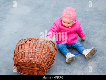 A year-old child in a pink jacket and hat sits on the concrete next to a wicker basket - Stock Photo