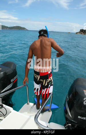 Seychellian man preparing to snorkel, Felicite Island, Seychelles. - Stock Photo