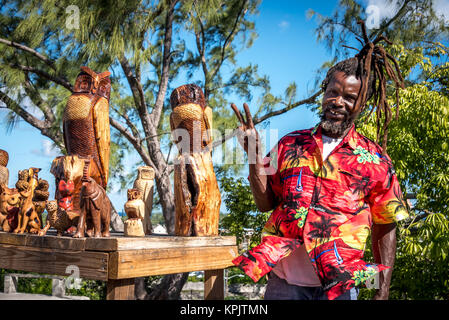 A smiling wood carver craftsman with carved animals on display, selling wooden owls, elephant carvings to tourists - Stock Photo