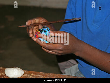 Candlemaker with carved colourful elephant shaped candle, Kingdom of Swaziland. - Stock Photo