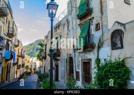 Typical neighborhood street on the island of lipari with its flowering pots and ancient constructions - Stock Photo