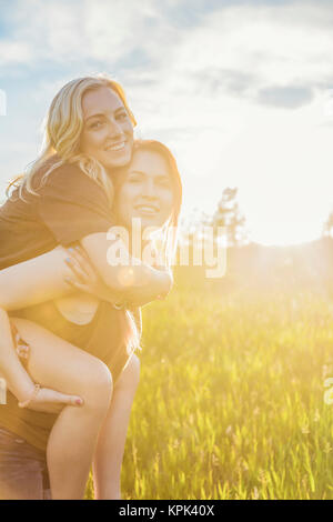 Two friends walking in a park, one giving the other a piggy back ride and posing for the camera; Edmonton, Alberta, - Stock Photo