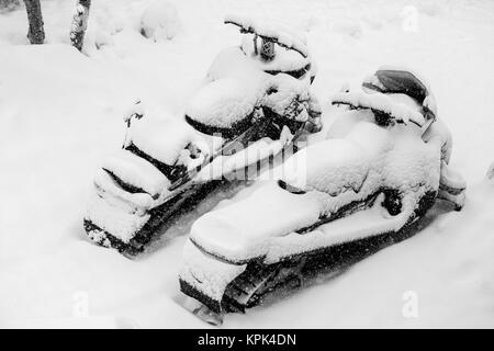 Two snowmobiles covered in snow, Grand Targhee Resort; Wyoming, United States of America - Stock Photo