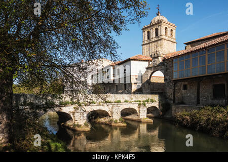 Puente del Portazgo, Puerta del Portazgo with 14th century Colegiata de San Miguel in background; Aguilar de Campoo, - Stock Photo