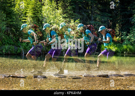 Multiple exposure of a female hiker with trekking poles leaps from rock to rock in a shallow stream and splashes - Stock Photo