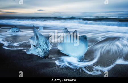 Jagged pieces of broken ice laying on the sandy shore at the edge of the ocean water; Iceland - Stock Photo