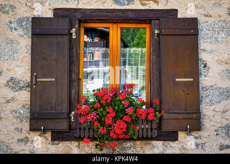 Close-up of Swiss chalet window with flower pot; La Fouly, Val Ferret, Switzerland - Stock Photo