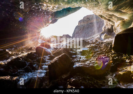 The sun shines into a cave beneath the ice of Root Glacier in Wrangell-St. Elias National Park; Alaska, United States - Stock Photo